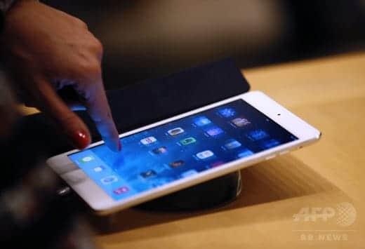 アップルストアでタブレット端末の「iPad」を操作する人