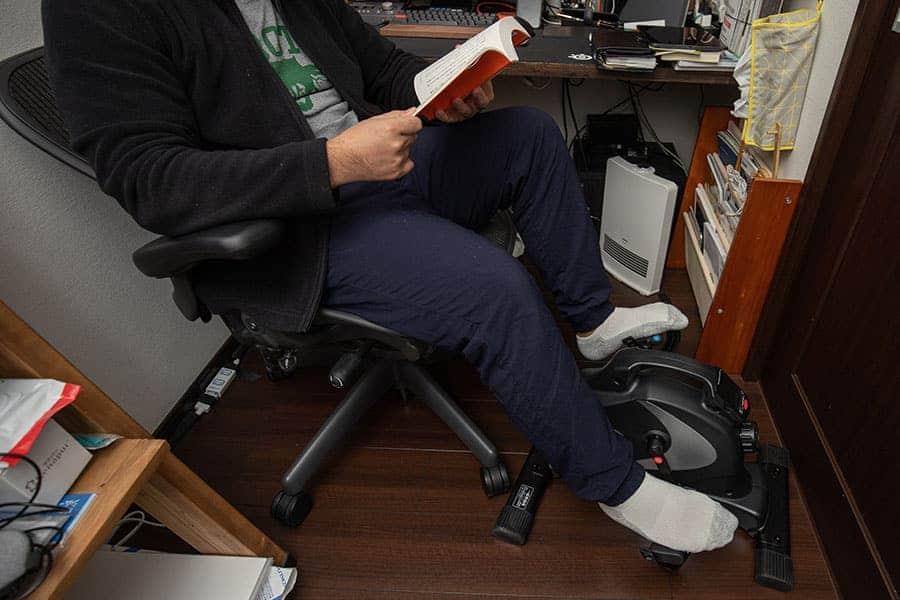仕事部屋のアーロンチェアで本を読みながらサイクリング運動