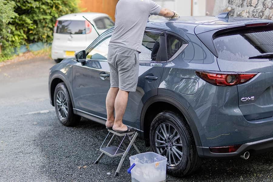 踏み台を使ってCX-5の屋根を洗っている写真