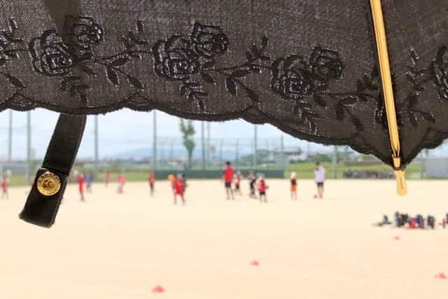 日傘でサッカーを観戦
